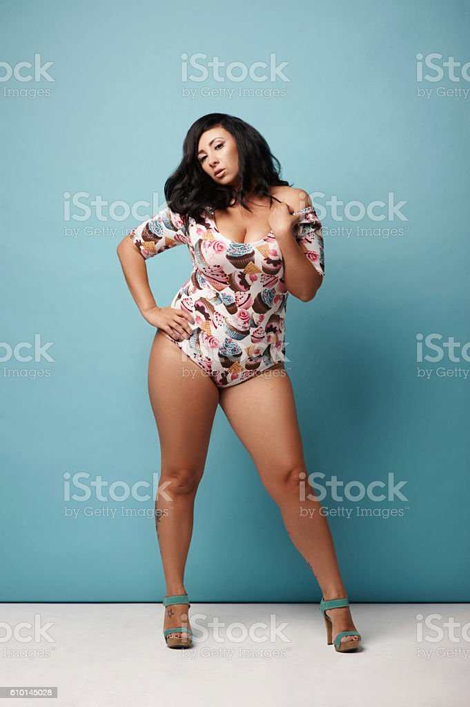 curvy woman with raven hair in trendy combidress posing against stock photo