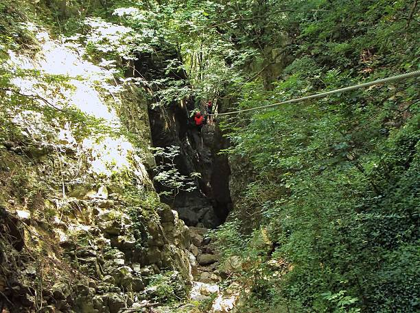 Cusano Mutri - Percorso avventura Conca Torta Cusano Mutri, Benevento, Campania, Italy - June 26, 2016: zip-lining adventure hikers along the route of the Gorges of Conca cake. These are Reviola gorges carved by the river, a tributary of Titerno River, which runs between Mount Calvary and the upper area of the village of Cusano Mutri. percorso stock pictures, royalty-free photos & images