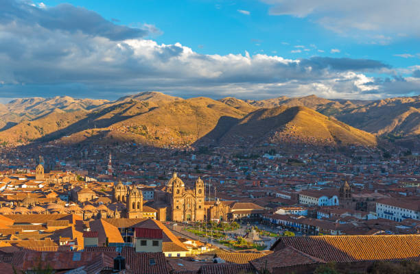 Cusco Cityscape at Sunset The cityscape of Cusco, the ancient Inca capital, with the Andes mountain range in the background at sunset, Peru. peruvian culture stock pictures, royalty-free photos & images