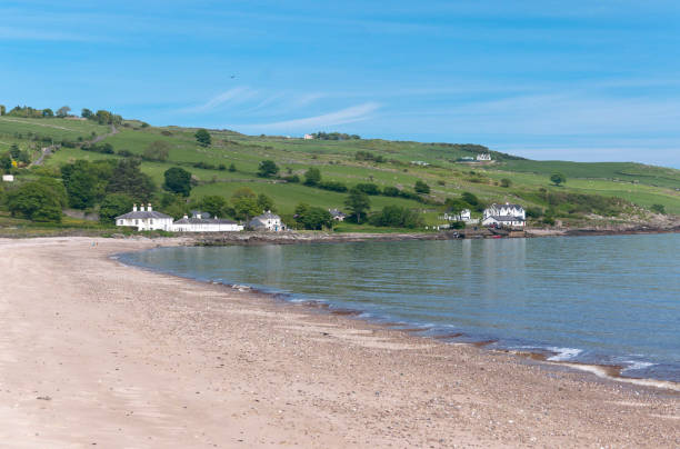 """Cushendun Beach View North Northwest Cushendun (from Irish: Cois Abhann Doinne, meaning """"foot of the River Dun"""") is a small coastal village in County Antrim, Northern Ireland. It sits off the A2 coast road between Cushendall and Ballycastle. It has a sheltered harbor and lies at the mouth of the River Dun and Glendun, one of the nine Glens of Antrim. Seen here is the beach, harbor, Torr Road climbing distant hills of the Antrim coast. Cushendun is part of Causeway Coast and Glens district.  Cushendun Caves are featured in the """"Game of Thrones"""" series. cushendun michael stephen wills stock pictures, royalty-free photos & images"""