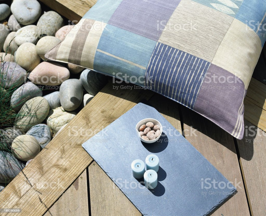A cushion and rocks on a sunny patio stock photo