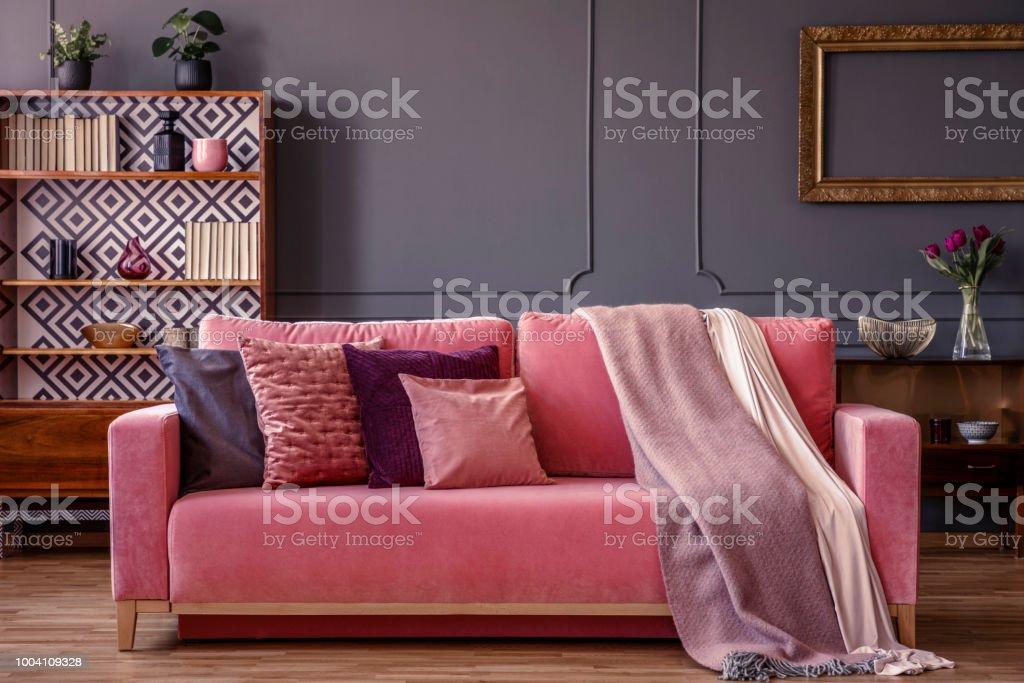Woonkamer Met Bibliotheek : Kussens en dekens op een roze fluwelen sofa in een luxe grijs