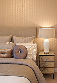 a corner of a bed dressed by an interior designer for an expensive new home. Silk cushions, bedclothing and headboard are in shades of brown, gold and cream. A matching lamp sits on a glass fronted bedside table.