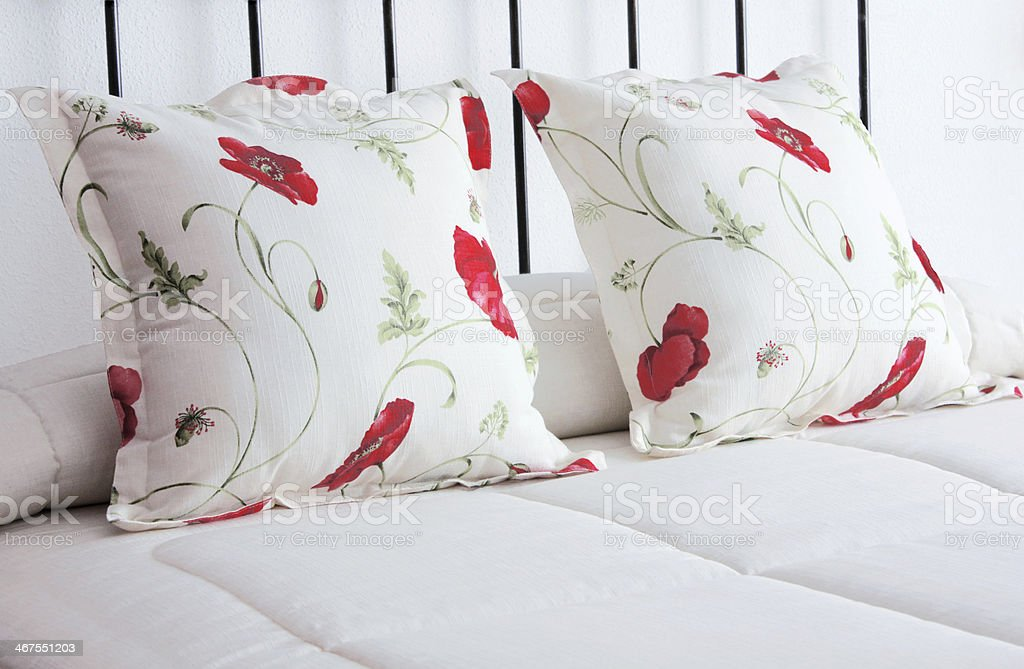 Red flower cushions on a white design bed headboard.