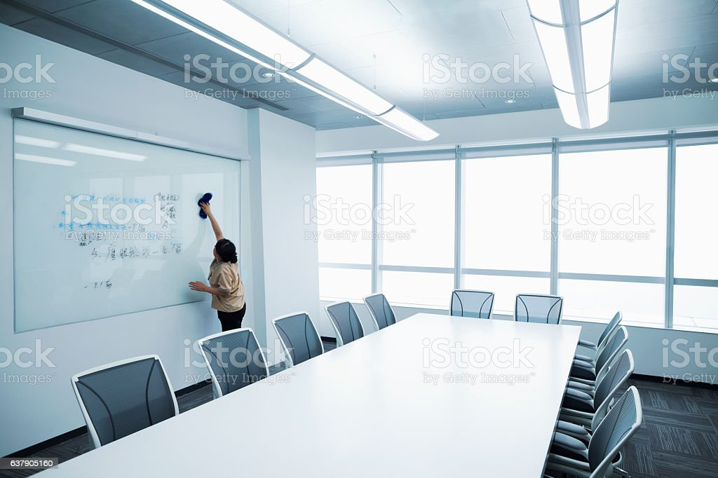 Custodial staff wiping white board clean in meeting room stock photo
