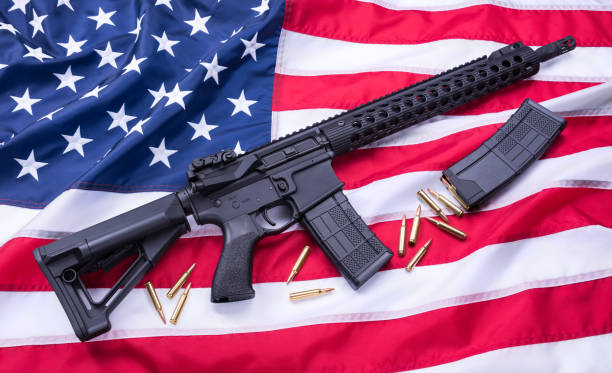 Custom built AR-15 carbine, bullets and a magazine on American flag surface, background. Studio shot. Custom built AR-15 carbine, bullets and a magazine on American flag surface, background. Studio shot ar 15 stock pictures, royalty-free photos & images