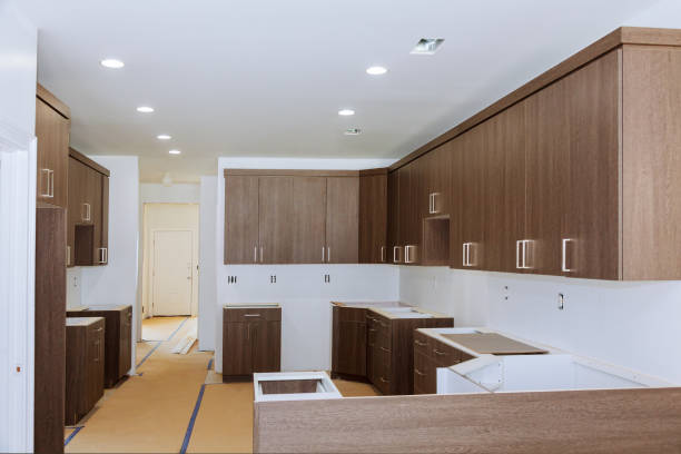 Custom kitchen cabinets in various stages of installation base for island in center stock photo