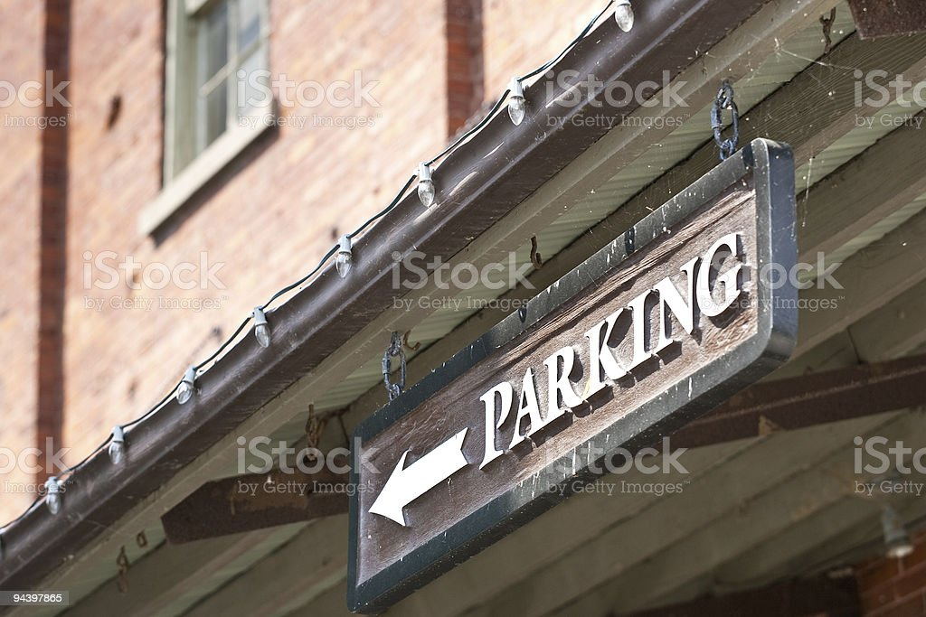 Custom Parking sign with arrow on side of building royalty-free stock photo