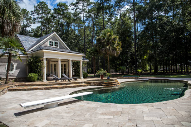 Custom pool House behind a landscaped estate with a large swimming pool and hot tub Custom pool House behind a landscaped estate with a large swimming pool and hot tub backyard pool stock pictures, royalty-free photos & images