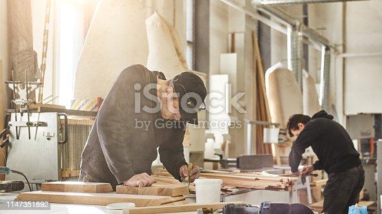 Woodwork and furniture making concept. Carpenter in the workshop varnishes furniture cabinet. Horizontal shot