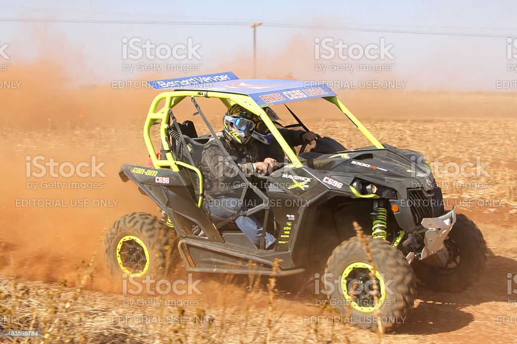 Custom twin seater rally buggy kicking up trail of dust stock photo