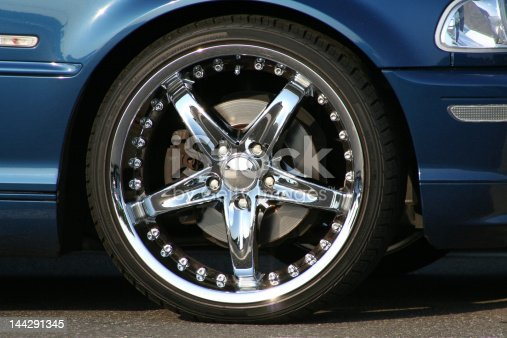 Custom chrome wheel and tire on blue sport sedan