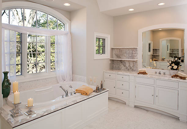 custom white toned master bathroom with hot tub tub. - bathroom renovation stock photos and pictures