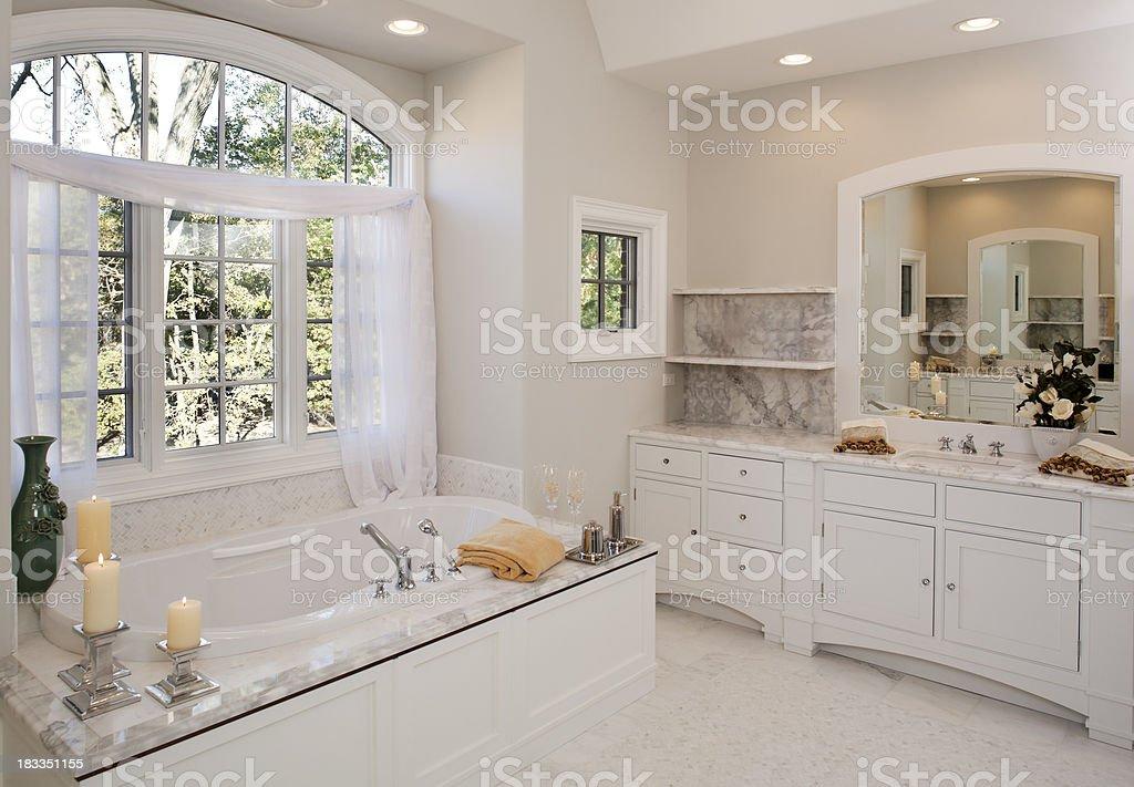 Custom white toned master bathroom with jacuzzi tub. stock photo