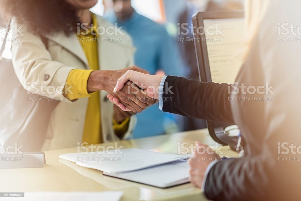 Customer and bank teller shaking hands - foto de acervo
