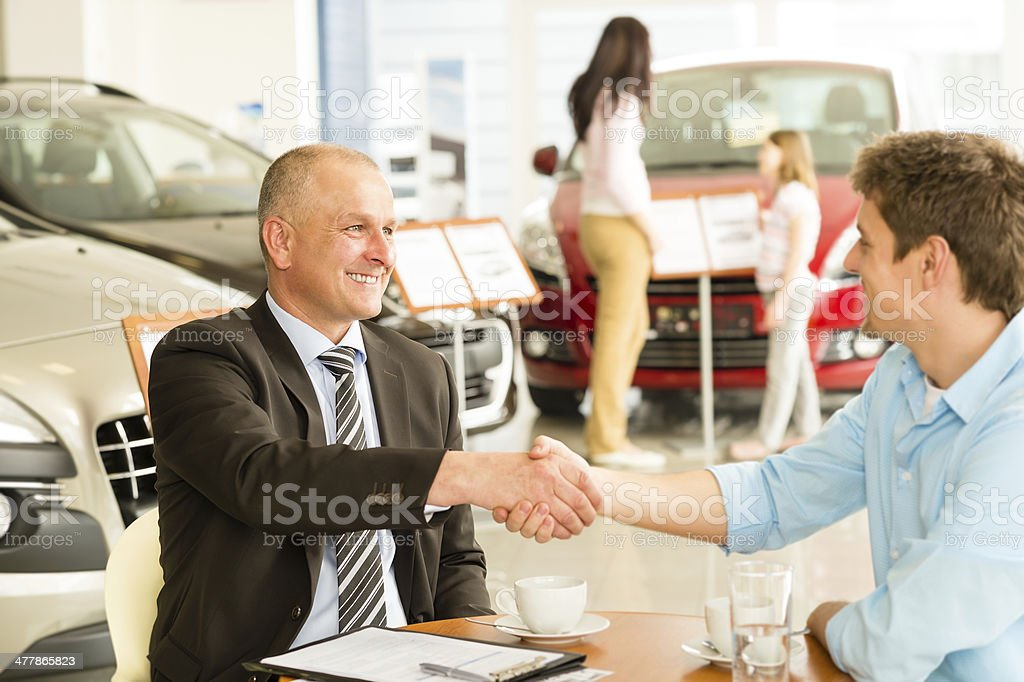 Customer and car salesman shaking hands stock photo