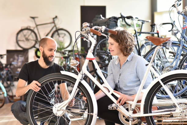 customer and dealer in bicycle shop - purchase and repair of bicycles - customer service customer and dealer in bicycle shop - purchase and repair of bicycles - customer service bicycle shop stock pictures, royalty-free photos & images