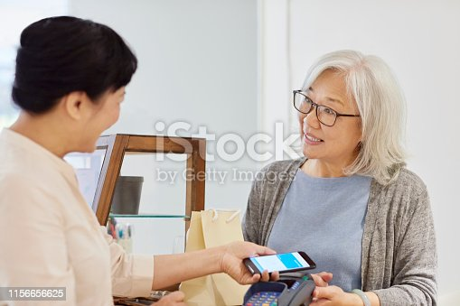 istock Customer and owner interacting during payment 1156656625
