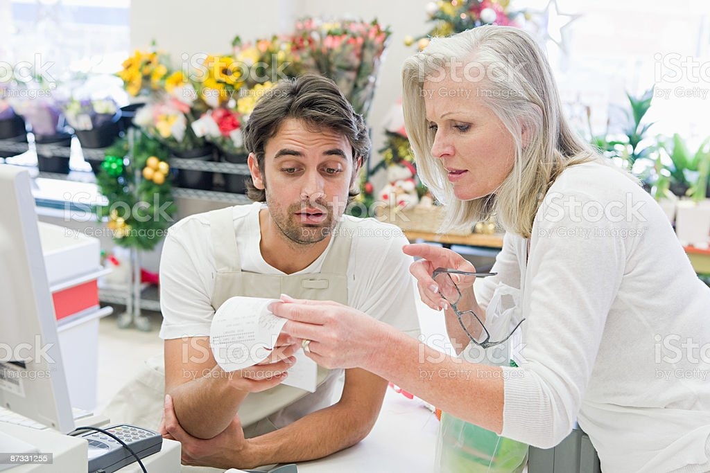 Customer and sales assistant looking at receipt royalty-free stock photo