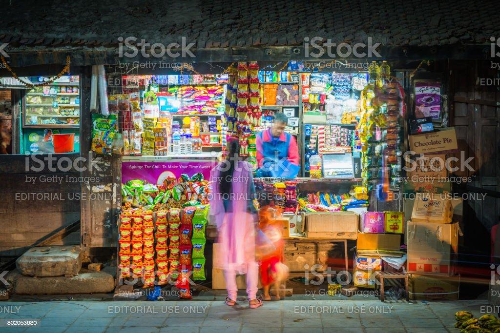Customer and shopkeeper at illuminated roadside general store Kathmandu Nepal stock photo