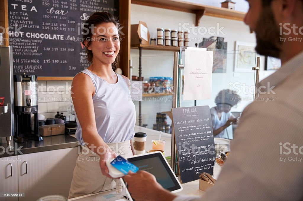 Customer at coffee shop pays smiling waitress with card stock photo