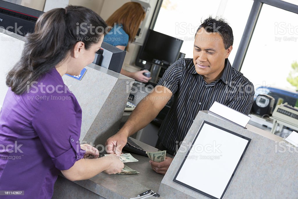 Customer at the bank getting money from teller stock photo
