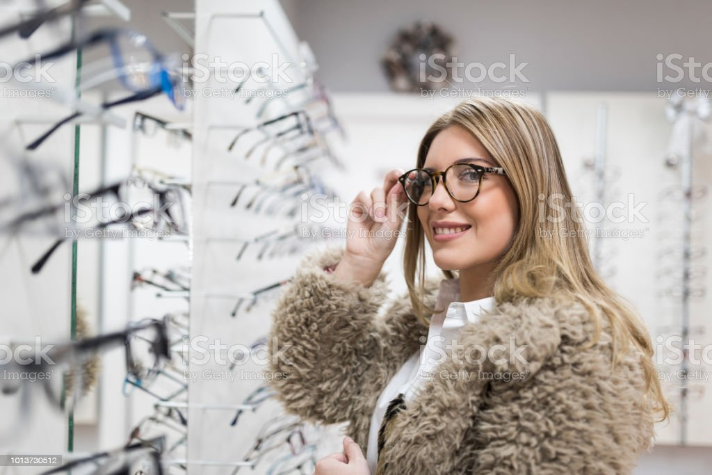 Customer blonde woman in optical store trying on glasses stock photo