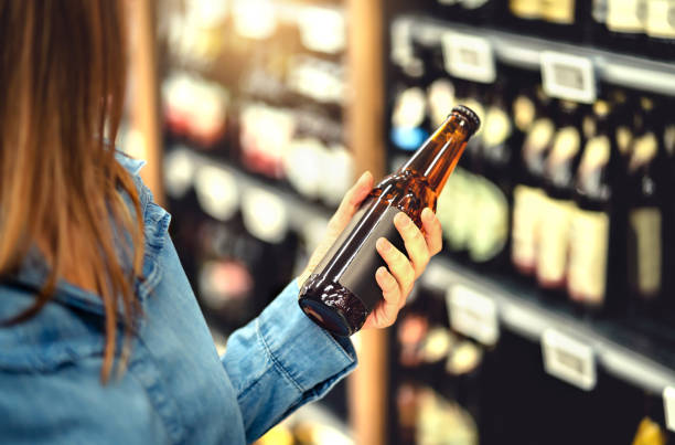Customer buying beer in liquor store. Lager, craft or wheat beer. IPA or pale ale. Woman at alcohol shelf. Drink section and aisle in supermarket. Lady holding bottle in hand. Drink business. Customer buying beer in liquor store. Lager, craft or wheat beer. IPA or pale ale. Woman at alcohol shelf. Drink section and aisle in supermarket. Lady holding bottle in hand. Drink business concept. pilsner stock pictures, royalty-free photos & images