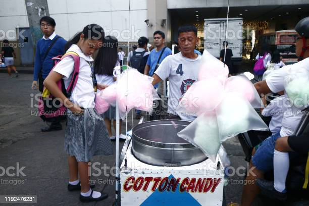 Customer buys colorful cotton candy from a street food vendor picture id1192476231?b=1&k=6&m=1192476231&s=612x612&h=hcj2jb4u71iqgt5m0i0 mg kk 4oael1ud6pgrmxiou=