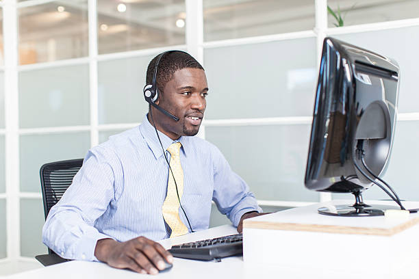 Customer care representative wearing headset and typing stock photo