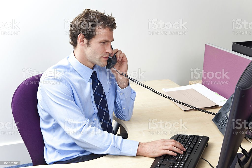 Customer care worker in an office on the telephone stock photo