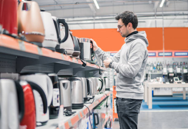 customer chooses a kettle in supermarket mall - happy person buy appliances stock photos and pictures