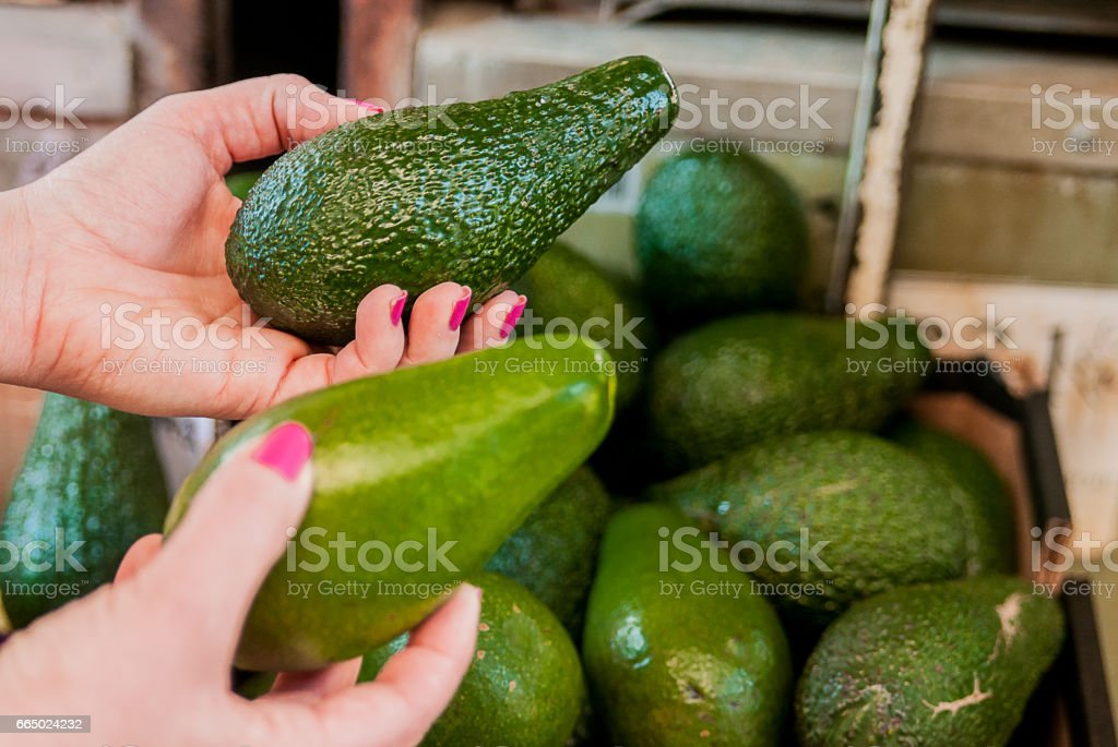 customer choosing avocados in the supermarket. stock photo