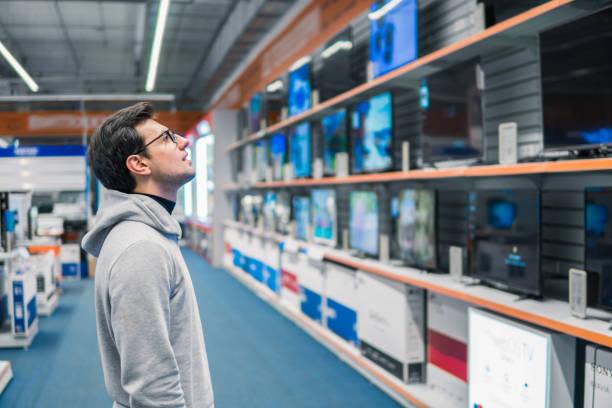 klant kiezen grote koelkasten in huishoudelijke apparaten sectie - huishoudelijke apparatuur stockfoto's en -beelden