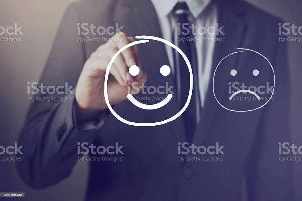 Customer choosing to write satisfied face over unhappy face stock photo