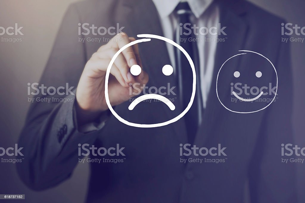 Customer choosing to write unhappy face over happy face stock photo