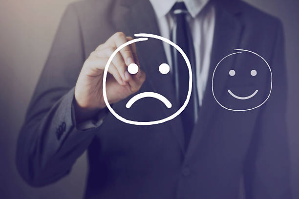 customer choosing to write unhappy face over happy face - disappointment stock pictures, royalty-free photos & images