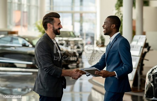 Portrait of a customer closing a deal with a salesman at a car dealership and looking very happy handshaking