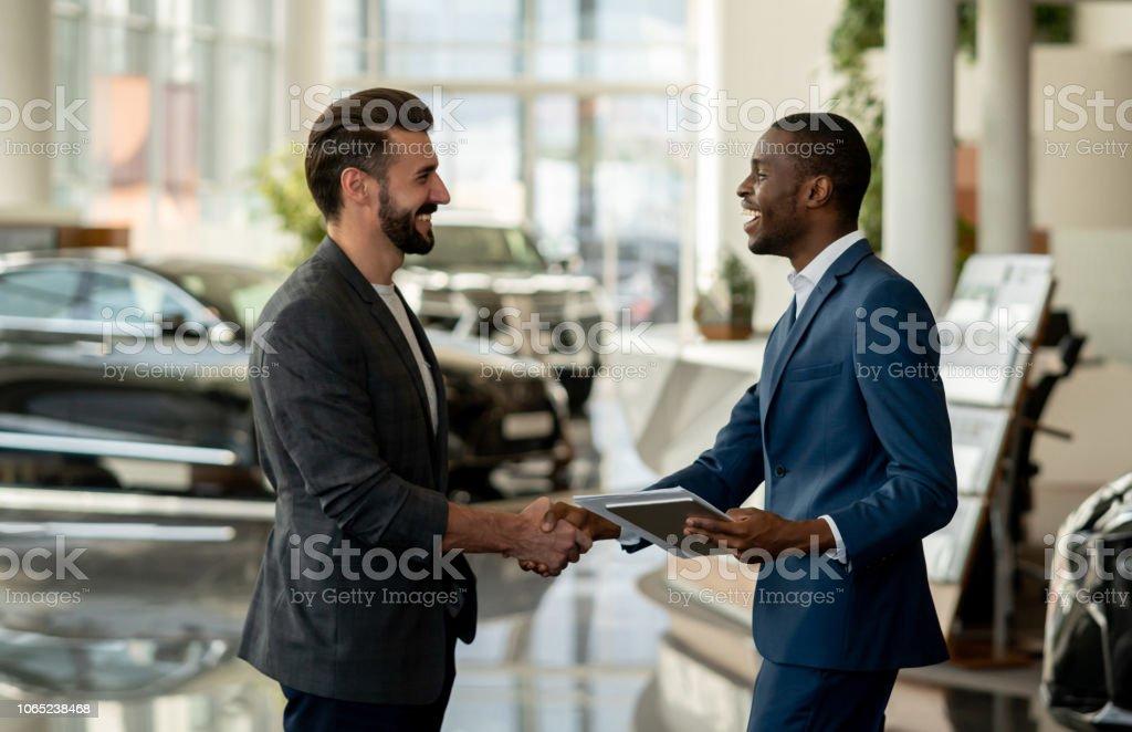 Kunden schließen einen Vertrag mit einem Verkäufer bei einem Autohändler – Foto
