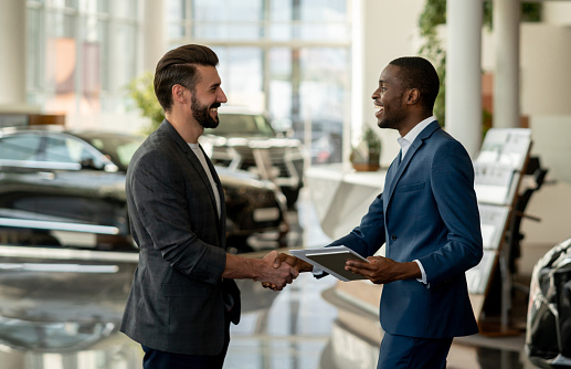 Customer Closing A Deal With A Salesman At A Car Dealership - Fotografie stock e altre immagini di Adulto