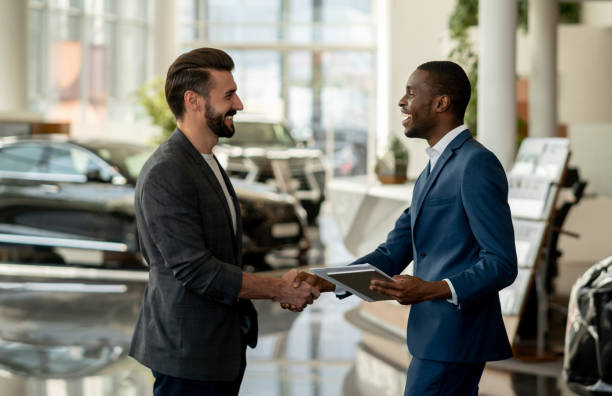 Customer closing a deal with a salesman at a car dealership Portrait of a customer closing a deal with a salesman at a car dealership and looking very happy handshaking car salesperson stock pictures, royalty-free photos & images