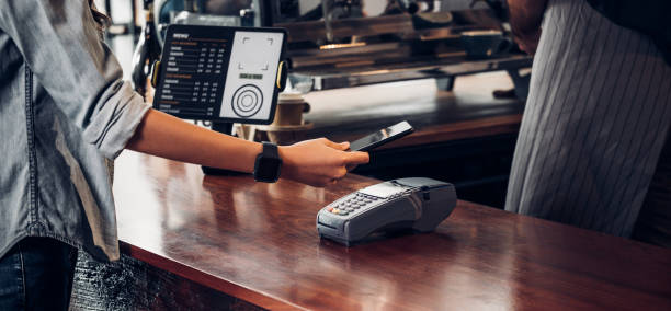 customer contactless payment for drink with mobile phon at cafe counter bar,seller coffee shop accept payment by mobile.new normal lifestyle concept stock photo