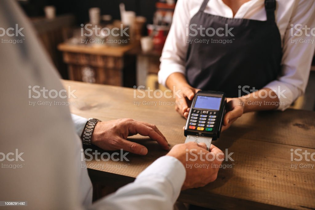 Customer doing payment of coffee by credit card at cafe stock photo
