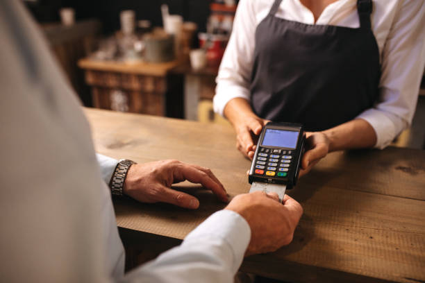 Customer doing payment of coffee by credit card at cafe Cropped shot of male customer paying for coffee by credit card at cafe. Woman barista holding a credit card reader machine with man doing payment on cafe counter. inserting stock pictures, royalty-free photos & images