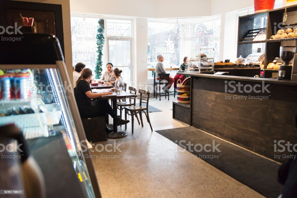 Customer enjoying time in a small local bakery shop. stock photo