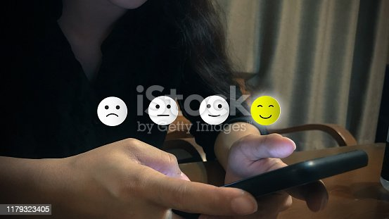 693589426 istock photo Customer experience concept. A woman using smartphone choose happy smile face icon. Depicts that customer is very satisfied. 1179323405