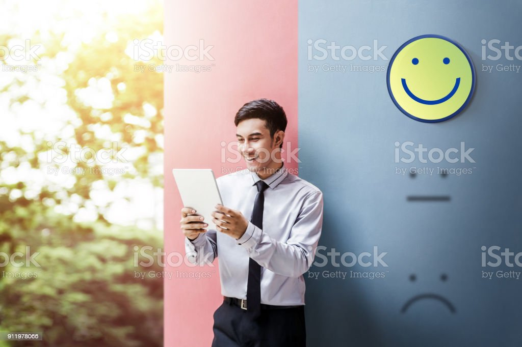 Customer Experience Concept, Happy Businessman Enjoying on digital Tablet with Smiley Face Rating for a Satisfaction Survey stock photo