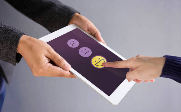 customer experience concept. happy client pressing a smiley face sign on digital tablet for online satisfaction survey - fedeltà foto e immagini stock
