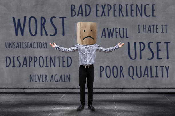 Customer Experience Concept, Unhappy Businessman Client with Sadness Emotion Face on Paper Bag, Blurred Concrete Wall with Wording of Negative Reviews as background Customer Experience Concept, Unhappy Businessman Client with Sadness Emotion Face on Paper Bag, Blurred Concrete Wall with Wording of Negative Reviews as background adulation stock pictures, royalty-free photos & images