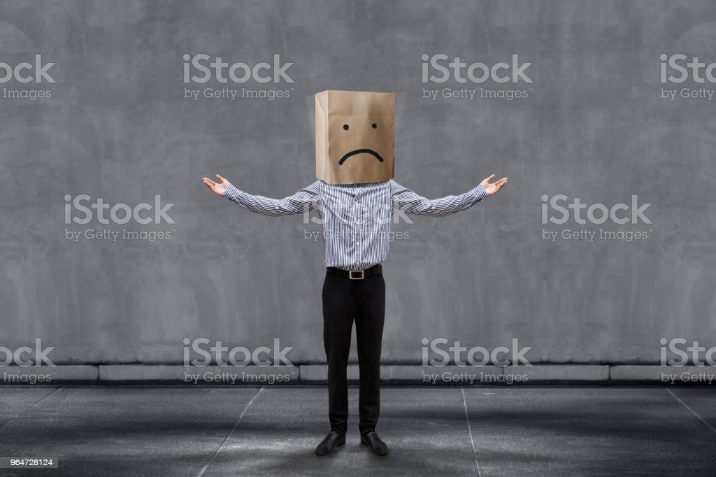 Customer Experience Concept, Unhappy Businessman Client with Sadness Emotion Face on Paper Bag, Arms up with meaning of Disappointed and Wondering. Concrete Wall as background royalty-free stock photo